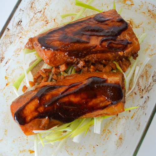 Two cod fillets in a baking dish topped with brown glaze