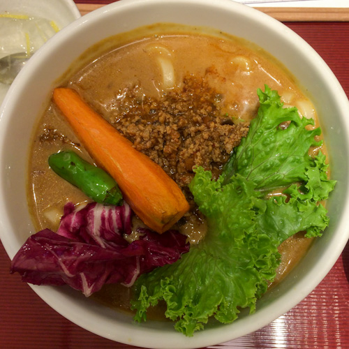 Bowl of Japanese curry udon with ground beef, lettuce, and a large carrot