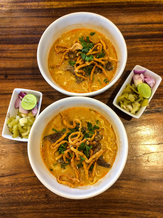 Overhead view of two bowls of khao soi with side dishes