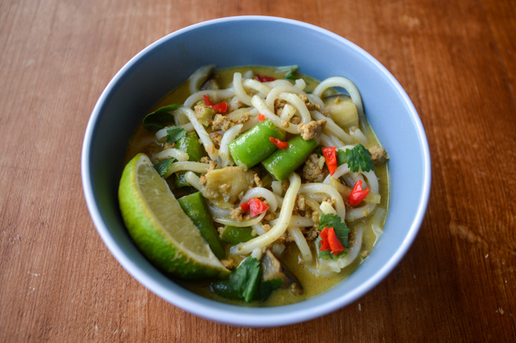 Blue bowl of khao soi curry udon with sugar snap peas, spicy red peppers and a lime wedge