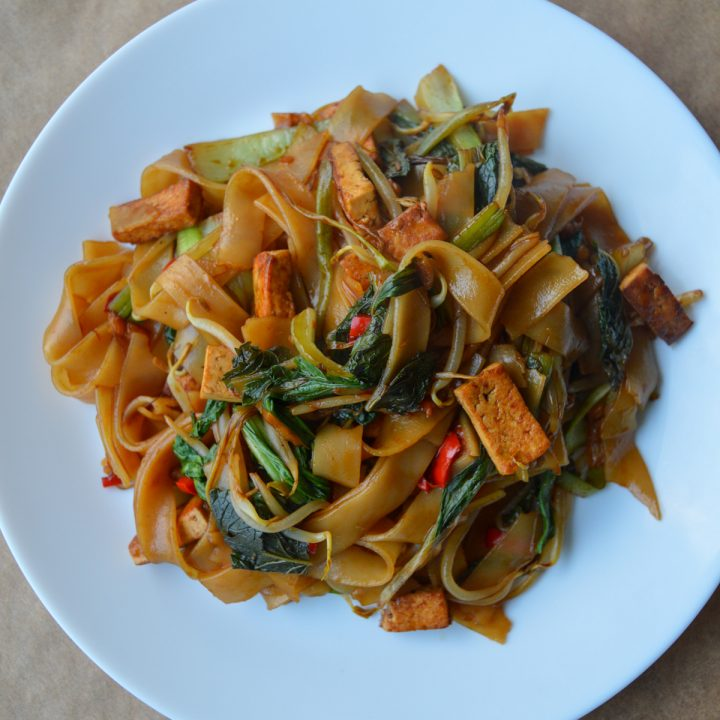White plate with a pile of vegetarian drunken noodles
