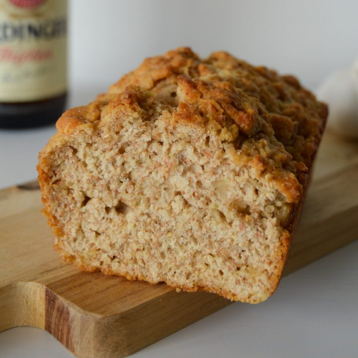 Loaf of whole wheat beer bread on a board with a beer in the background