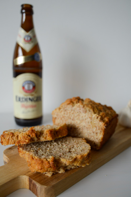 Half a loaf of beer bread on a small wood board in front of a bottle of wheat beer