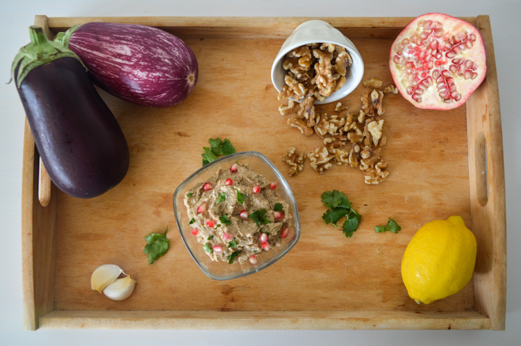 A wood tray with a dish of pkhali and all its ingredients: eggplant, garlic, walnuts, cilantro, lemon, and pomegranate