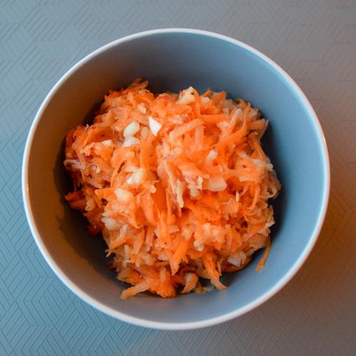 Blue bowl of shredded carrot apple salad