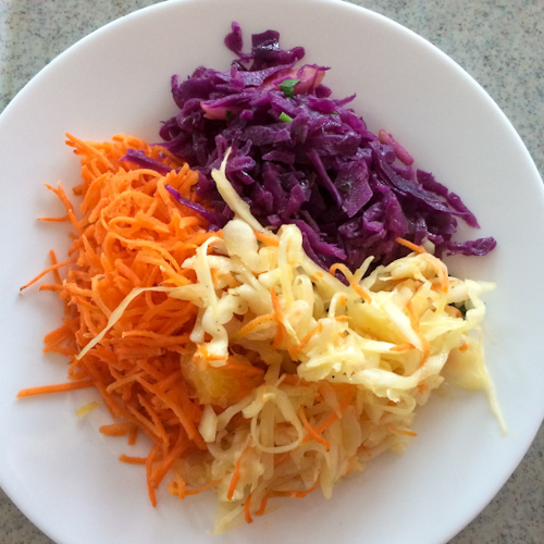 Plate of Polish salads including shredded carrots, red cabbage, and coleslaw