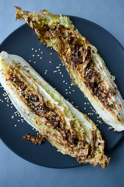 Two wedges of roasted napa cabbage topped with sesame seeds on a black plate