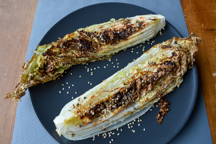 Angled view of two pieces of roasted napa cabbage with sesame seeds