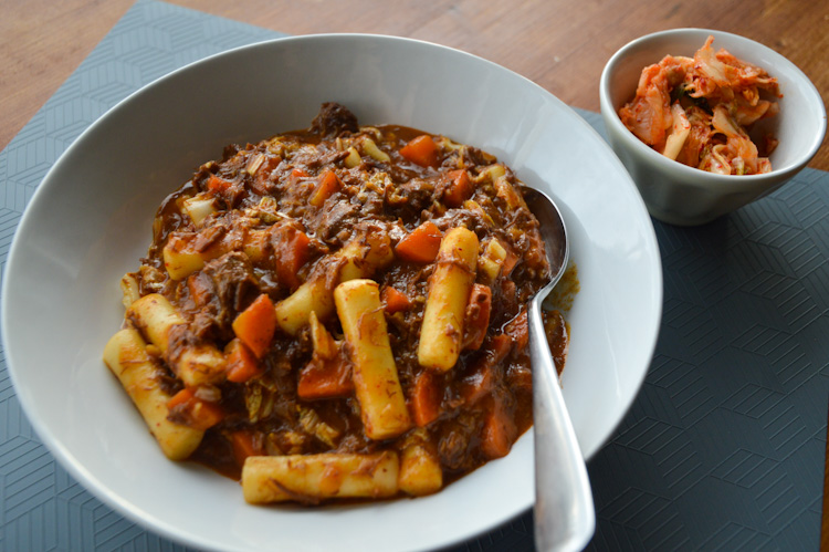Close up of a bowl of Korean beef stew with a spoon, and a small side bowl of kimchi