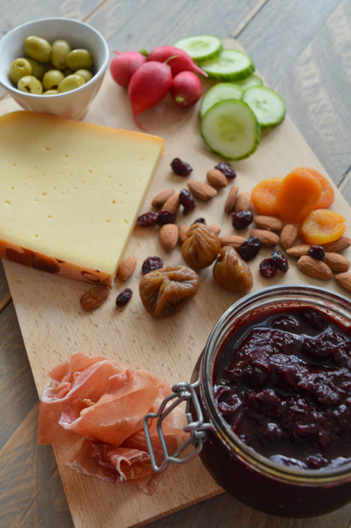 A wood board with everything you'd want: meat, cheese, nuts, dried fruit, olives, veg, and of course a jar of plum chutney