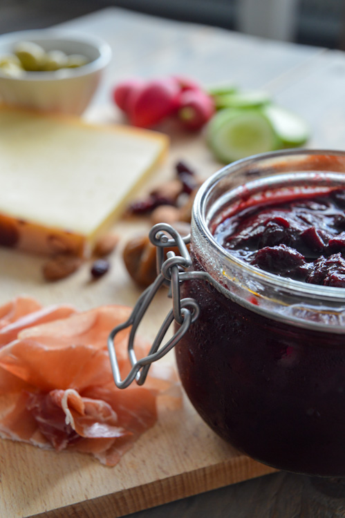 Close up of glass jar of plum chutney sitting on a wood board with other borrel snacks (meat, cheese, nuts, etc.)
