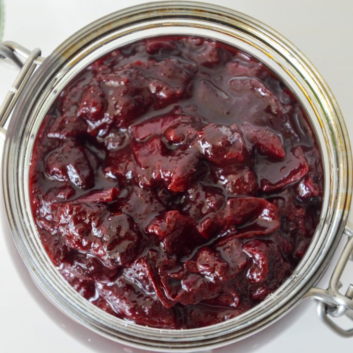 Top down view of glass jar with deep purple spiced plum chutney