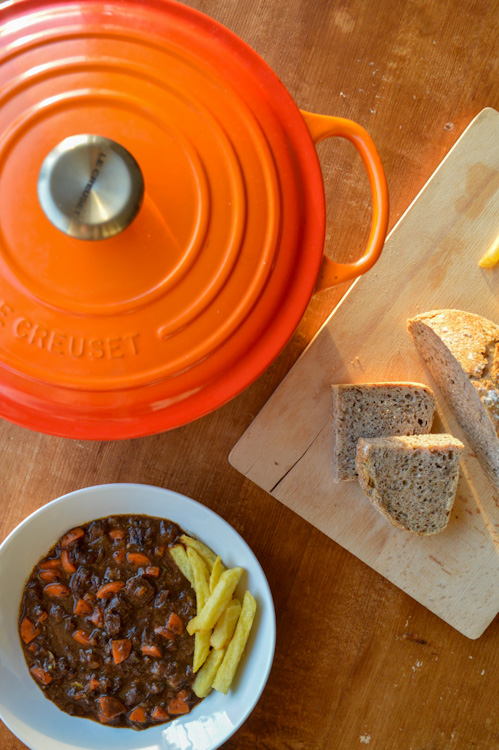 Overhead shot of a bowl of beef stew with fries, an orange Dutch oven, and a wood board with bread
