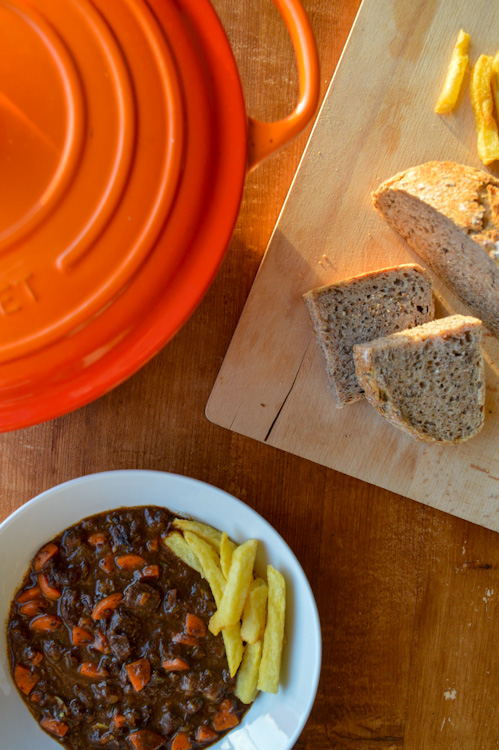 Overhead shot of a bowl of stoofvlees Flemish beef stew, an orange Dutch oven, and a wood board with bread and fries