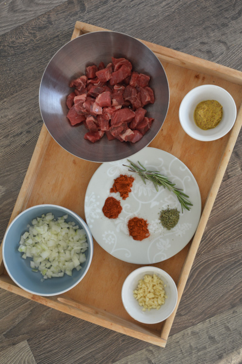 Overhead shot of stoofvlees ingredients including cubed beef, minced onions, minced garlic, mustard, herbs, and spices