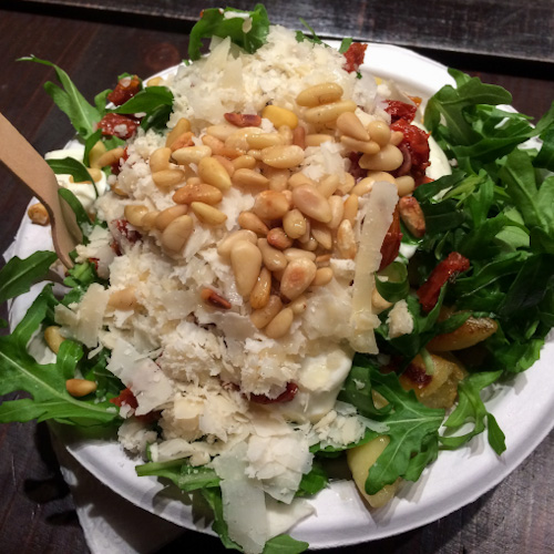 A bowl of Schupfnudeln with arugula, parmesan cheese, and pine nuts eaten at a Christmas Market in Cologne
