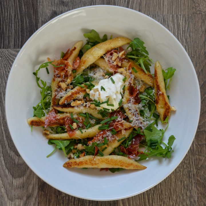 White bowl with cylindrical handmade dumplings, arugula, crispy ham, chopped walnuts, and sour cream