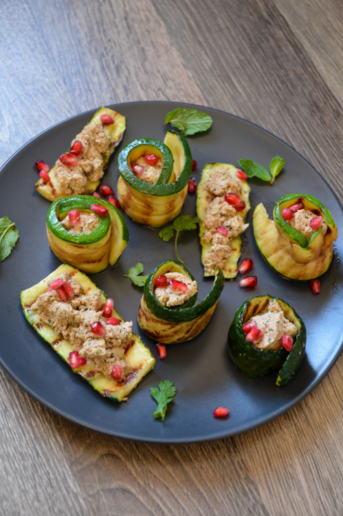 Black plate with 3 pieces of zucchini topped with Georgian walnut paste and 5 zucchini spirals with the paste in the center, all decorated with fresh green herbs and pomegranate seeds