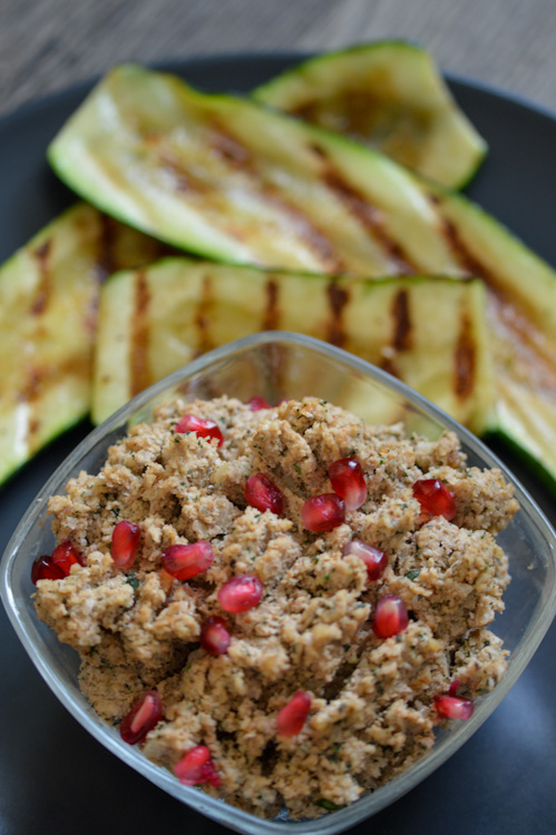 Georgian walnut spread topped with pomegranate seeds in a glass bowl in the foreground; behind it are a few pieces of grilled zucchini