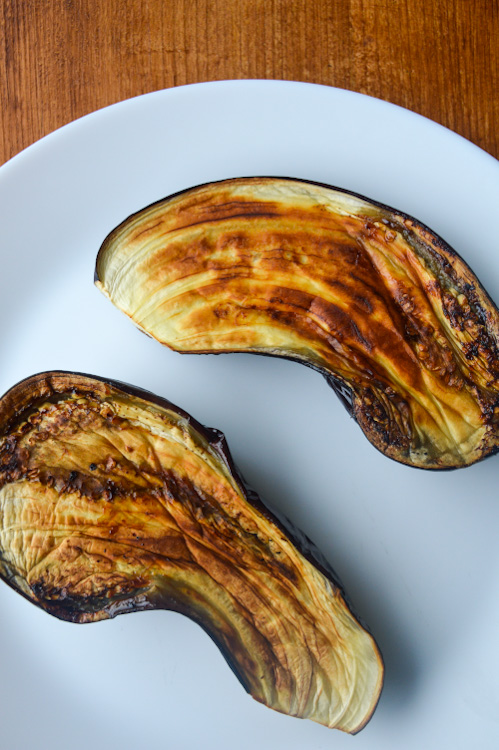 A white plate with two halves of roasted eggplant, nicely charred, face up