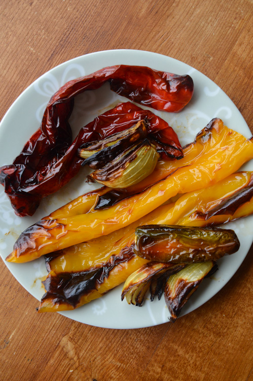 White plate holding charred, roasted red peppers, yellow peppers, onions, and jalapeno