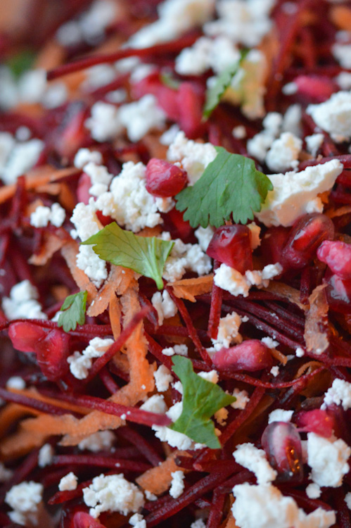 Super close shot of a beetroot salad with feta, carrots, pomegranate seeds, and parsley