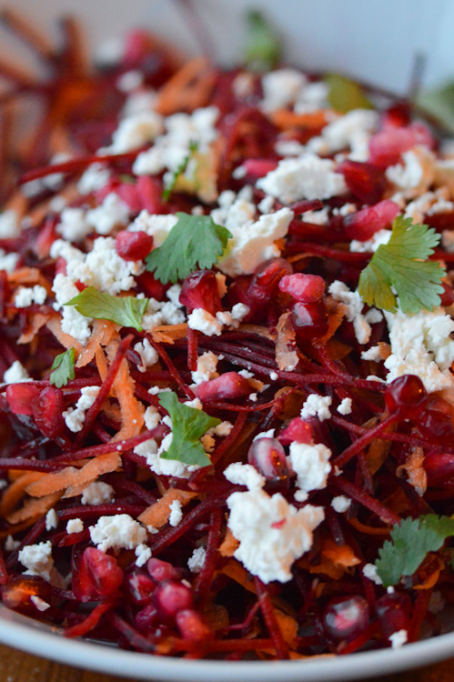Close up of bowl of beetroot salad with feta, carrots, pomegranate seeds, and parsley