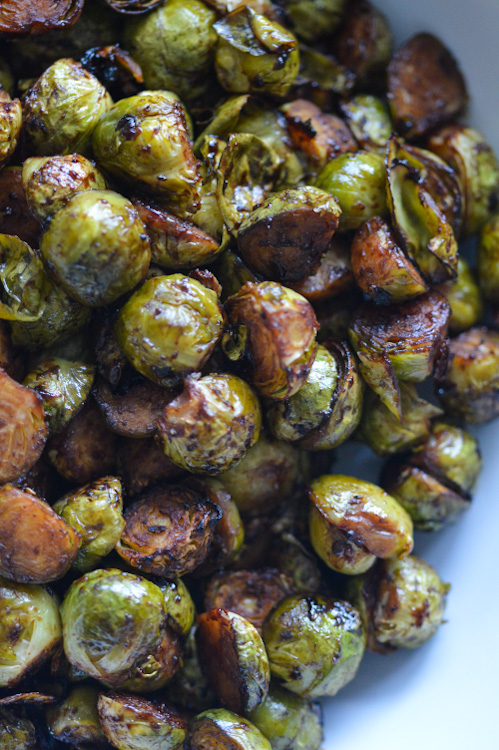 Close up of roasted brussels sprouts with soy sauce, hoisin, and sesame oil in a white bowl
