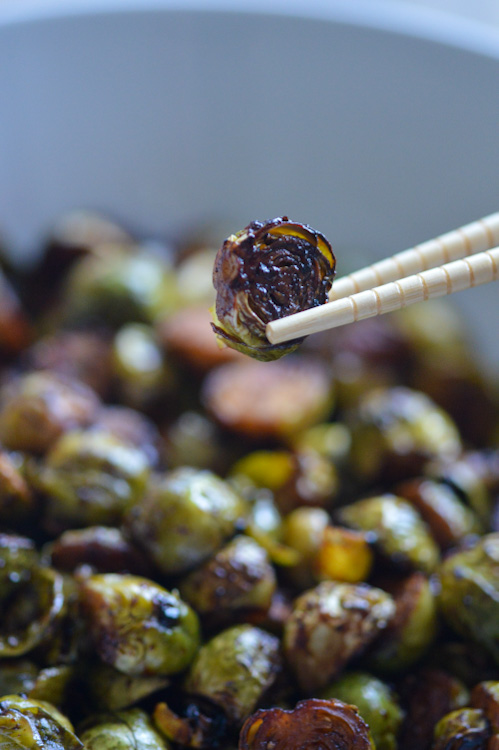 A single, browned Brussels sprout held above a bowl of its brethren with light colored chopsticks