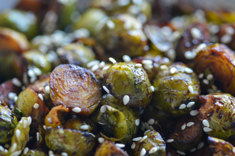 A super close shot of nicely browned roasted brussels sprouts topped with sesame seeds