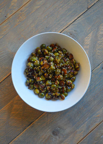 A white bowl of roasted Brussels sprouts sitting atop a wooden table
