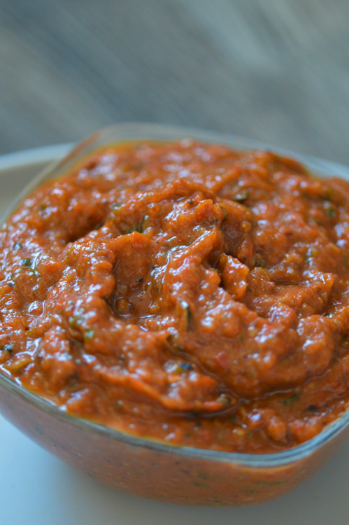 Close up of ajvar, a roasted red pepper and zucchini spread, in a glass dish