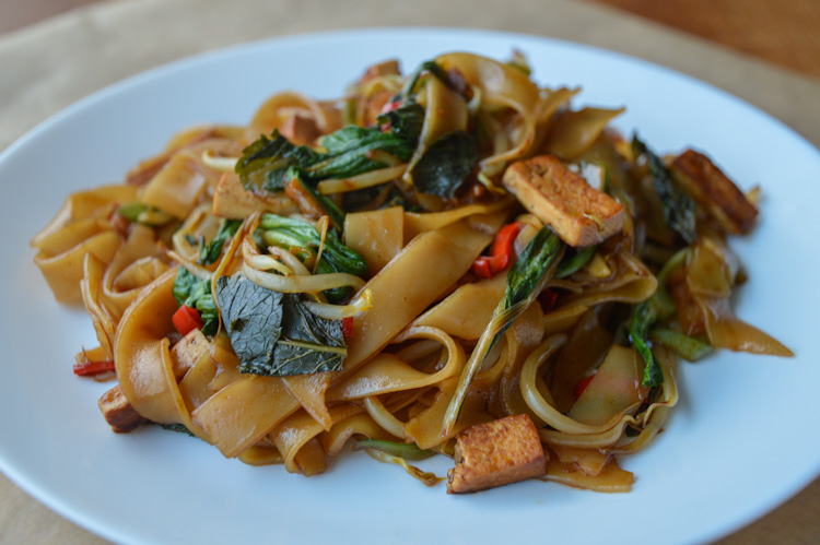 A white plate with a pile of vegetarian drunken noodles with tofu