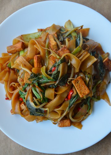 White plate full of vegetarian drunken noodles - wide rice noodles with tofu