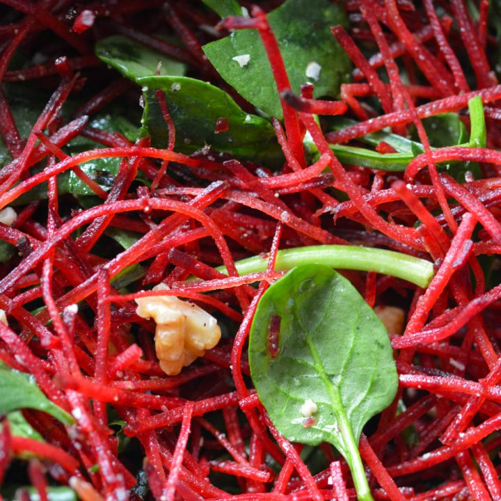 Close up shot of a salad of shredded beets, a few spinach leaves, and chopped walnuts