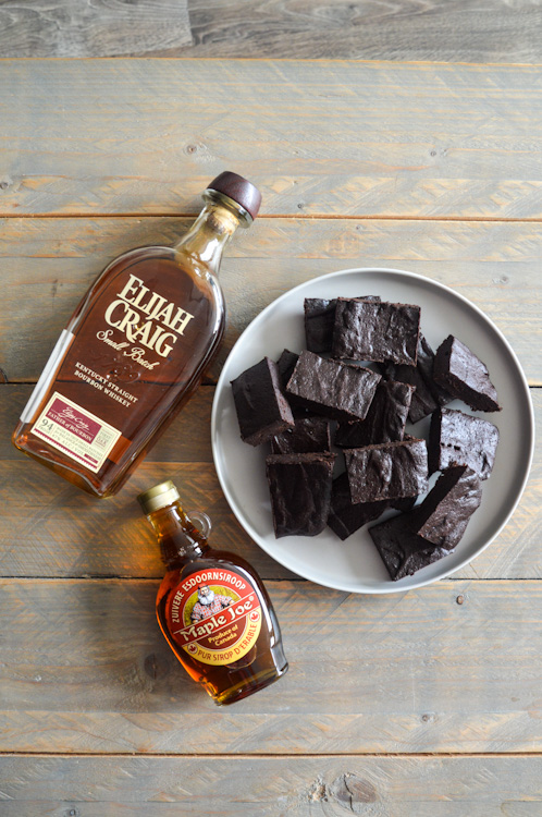 Plate of bourbon maple brownies laying next to bottles of bourbon and maple syrup on a wooden table