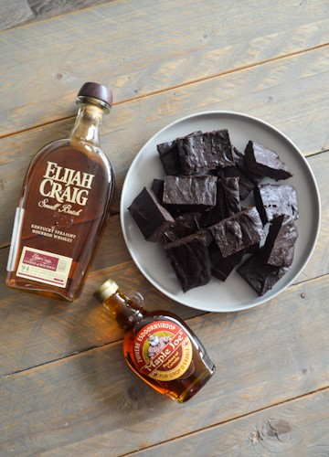 Plate of bourbon brownies laying next to bottles of bourbon and maple syrup on a wooden table