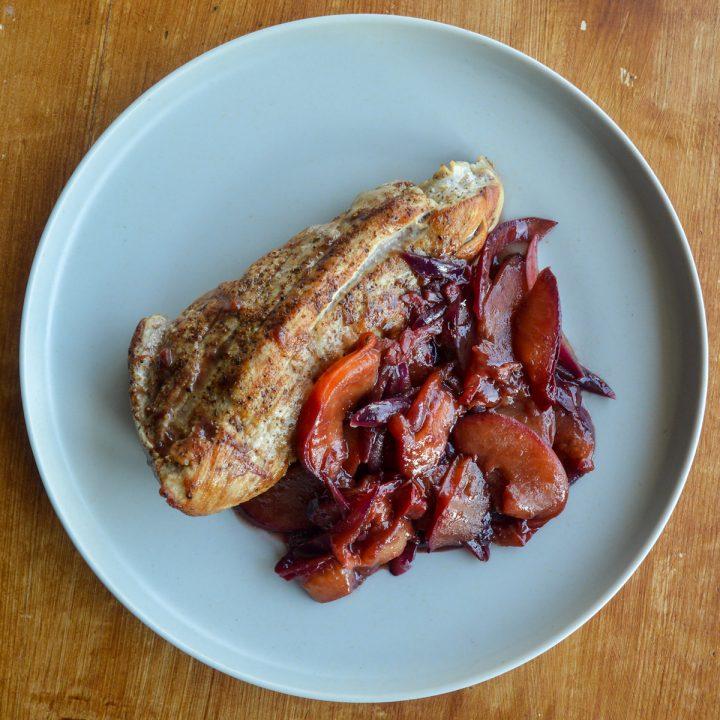 Pork tenderloin next to hoisin plum sauce on a plate
