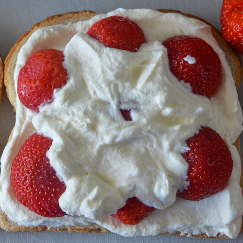 Piece of bread with whipped cream and strawberries