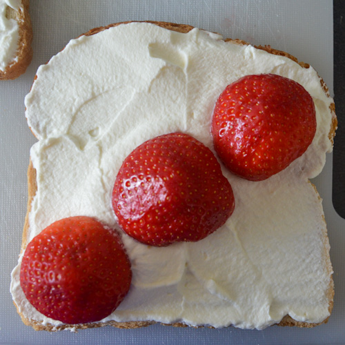 One piece of bread covered in whipped cream, with 3 strawberries running diagonally from bottom left corner to top right corner