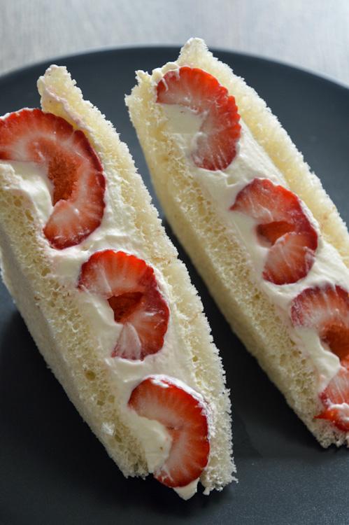 Strawberry sando (fruit sandwich Japanese style) standing upright on a black plate