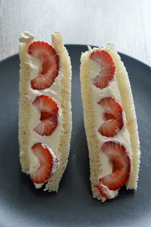 Strawberry sando (Japanese fruit sandwiches) - two pieces standing upright on a black plate